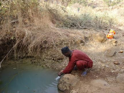 Prélèvement d'échantillon d'eau de source polluée par un enquêteur ARACF
